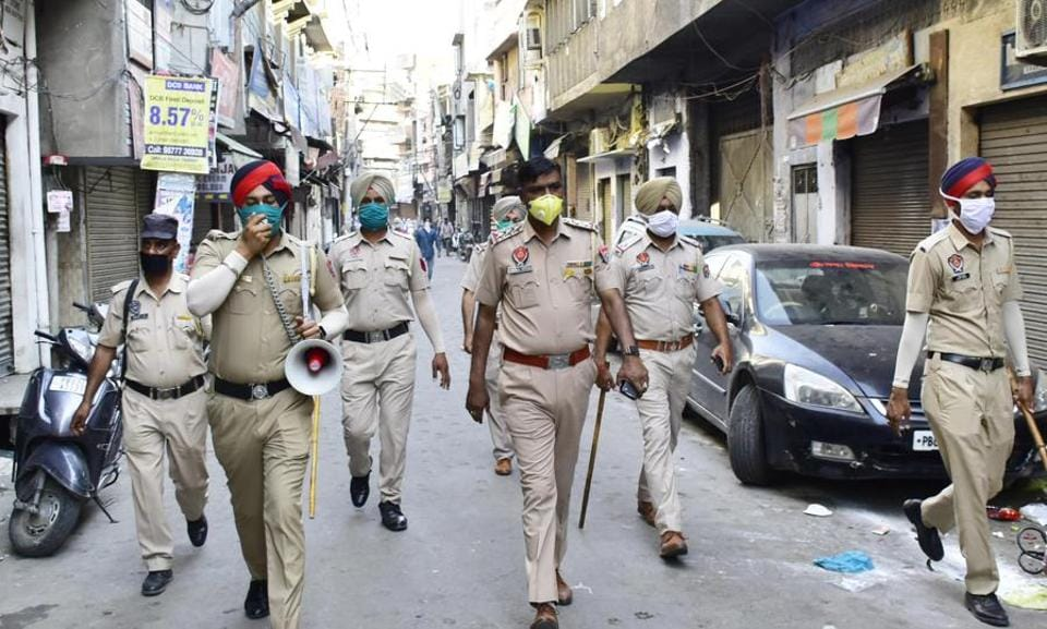 A Punjab police personnel makes an announcement urging people to stay at home, during lockdown to check the spread of coronavirus, at Ram Bagh area, in Amritsar.