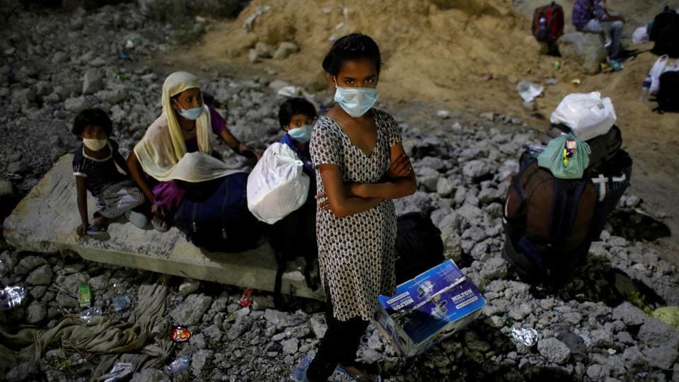 Children of migrant workers wearing protective face masks wait to cross the border to their home state of Uttar Pradesh, during an extended nationwide lockdown to slow the spread of the coronavirus disease (Covid-19), in New Delhi.