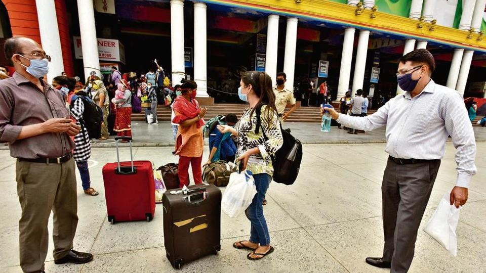 A passenger, upon arriving at the New Delhi railway station, sprays disinfectant over the luggage of his family members.