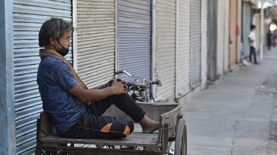 A migrant daily wage worker sitting on his cart infront of the closed market during lockdown, at Jama Masjid, in New Delhi.