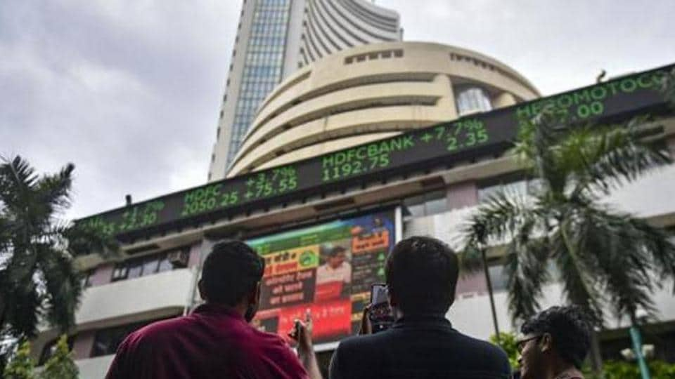 Bystanders react as they watch the stock prices displayed on a digital screen outside BSE building, in Mumbai