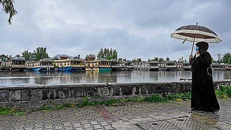 A woman walks on the banks of the Dal Lake in Srinagar.