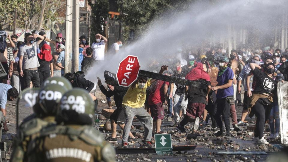 Demonstrators take cover after water cannons were launched at them. The municipality said in a statement that families were going hungry in the poorest sectors of El Bosque, a neighbourhood where many work informally, or not at all -- reported Reuters. (AP / PTI)