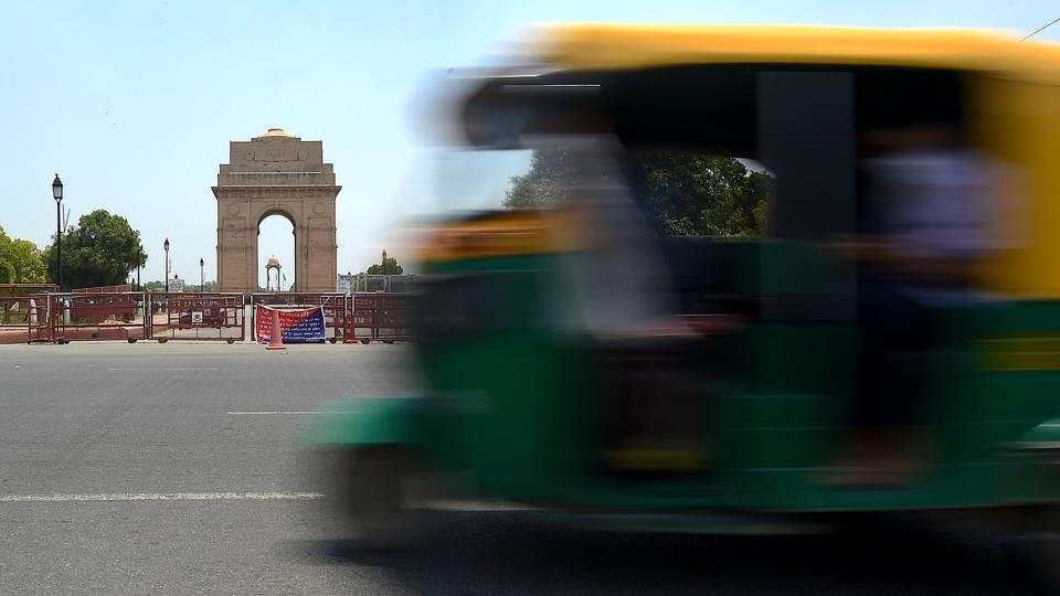 An auto-rickshaw drives past India Gate after the government eased restrictions imposed as a preventive measure against the coronavirus in New Delhi on May 19. After a nearly two month hiatus, the national capital took a restrained step towards normalcy with the revival of transport services and marketplaces. (Money Sharma / AFP)