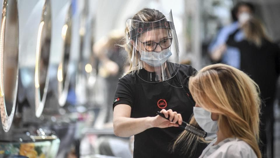 A woman gets her hair done at a hairdresser's in Milan on May 18. Telephones however rang incessantly in salons, as unkempt clients rushed to make themselves more presentable. (AP)