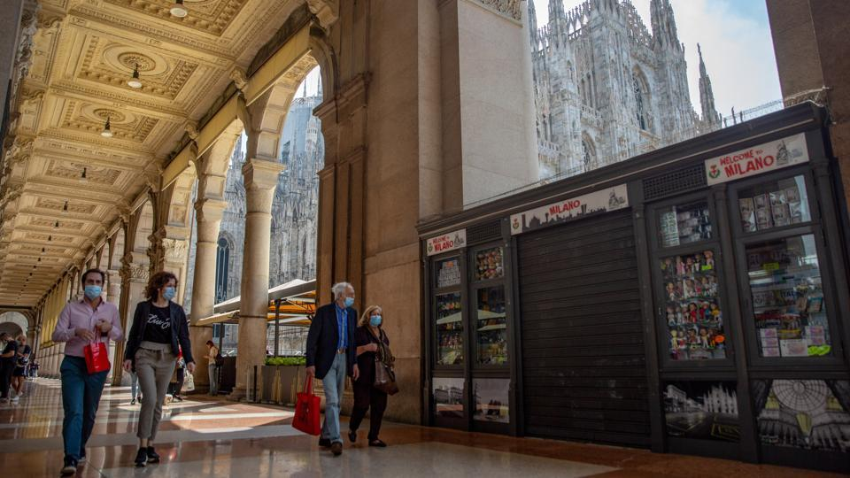 Pedestrians pass a closed tourist souvenir stall in view of the Duomo cathedral in Milan on May 18. Italian shoppers may have begun digging out their wallets as retail businesses reopen but foreign tourists, vital for the economy, remain absent. (Francesca Volpi / Bloomberg)