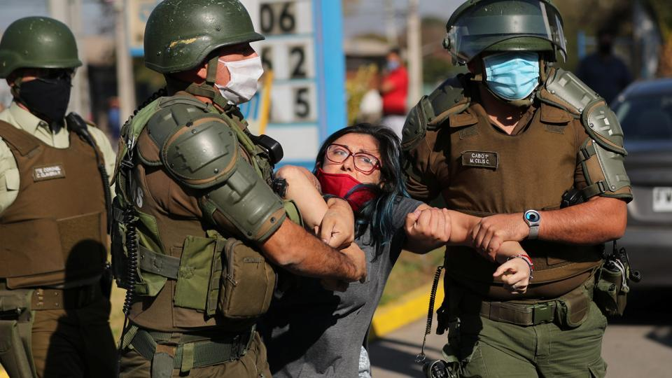 A woman is detained during the protest. Many of the demands lodged by protesters last year, from increased pensions to higher pay remain unresolved. (Ivan Alvarado / REUTERS)