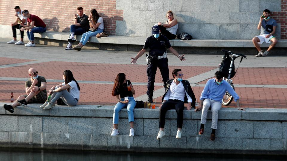 A police officer asks people drinking next to a canal to maintain social distancing in Milan on May 18. It was only day one, but major Italian cities noted higher traffic as people stepped out to catch up with friends. (Alessandro Garofalo / REUETRS)