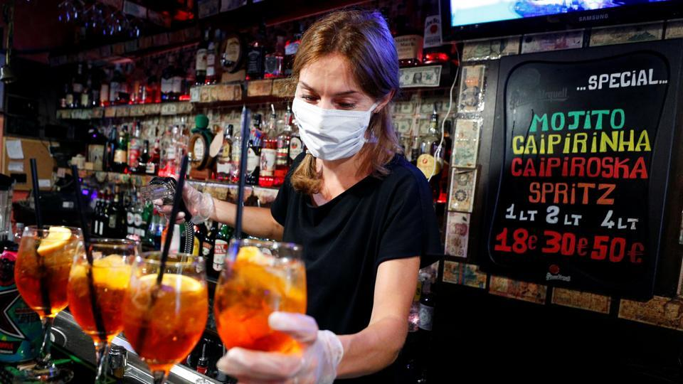 A bartender wearing a protective mask and gloves prepares cocktails in Rome's bohemian Trastevere neighbourhood on May 18. Customers will now once again be able to sip their beverage of choice at bars, albeit well spaced from other clients. Restaurants are able to serve as long as tables are kept at least 2 metres apart. (Guglielmo Mangiapane / REUTERS)
