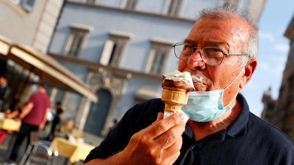 A man wearing a protective mask enjoys an ice-cream in Trastevere on May 18. Italy is scheduled to open up borders with Europe and allow free travel between the regions from June 3. (Guglielmo Mangiapane / REUTERS)