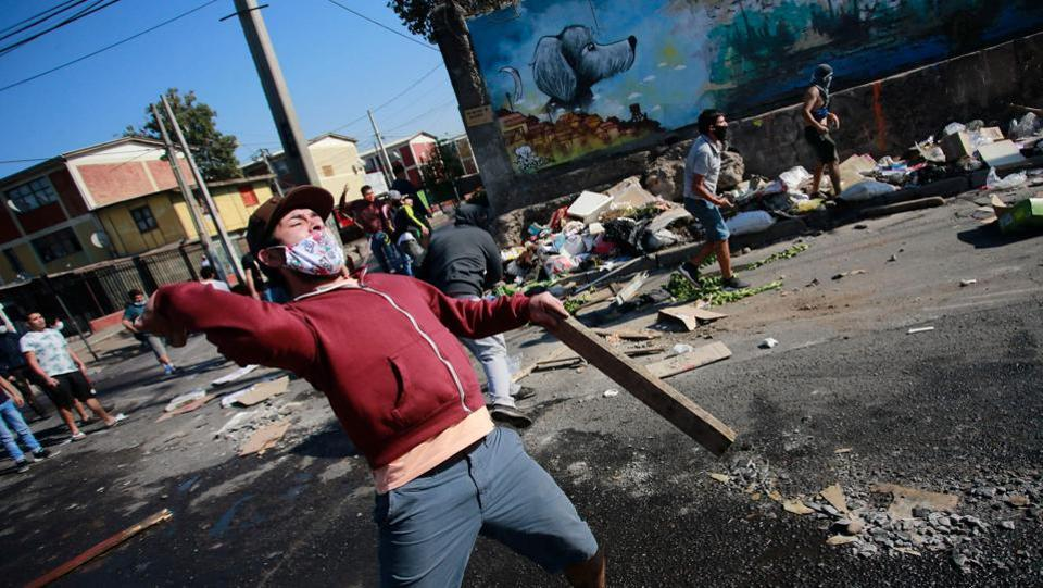 Demonstrators clash with riot police during a protest against the Chilean government amid the COVID-19 pandemic in Santiago on May 18. The protest erupted due to shortages in food and employment in one of the Chilean capital´s poorest neighbourhoods. (Pablo Rojas / AFP)