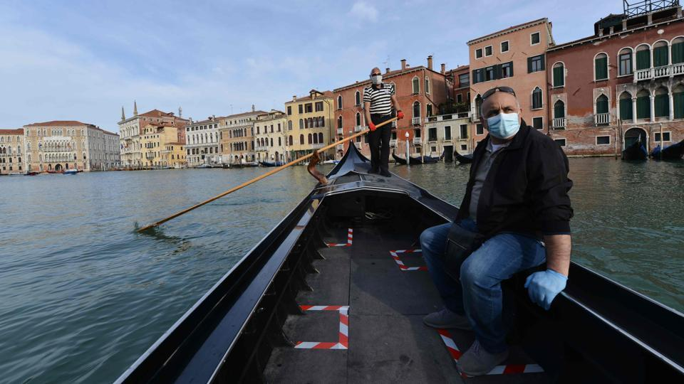A gondolier wearing a face mask transports his very first customer as service resumes at the San Toma embankment on a Venice canal on May 18 during Italy's eased exit from a lockdown aimed at curbing the spread of the COVID-19 infection that began 10 weeks ago on March 9. (Andrea Pattaro / AFP)
