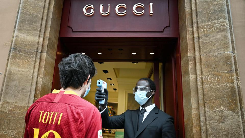 A fan of AS Roma wearing a Francesco Totti jersey undergoes a temperature check as he enters a Gucci store in Via dei Condotti in central Rome on May 18. Concerns linger among business owners that the reopening may not magic away their many problems as fears linger of the coronavirus keeping many Italians at home. (Alberto Pizzoli / AFP)