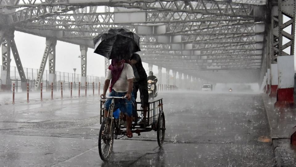 A cycle rickshaw crosses the iconic Howrah Bridge  in Kolkata in the middle of a heavy downpour. The landfall process has triggered intense rain and gusty winds and will continue for about four hours, according to IMD. (ANI)