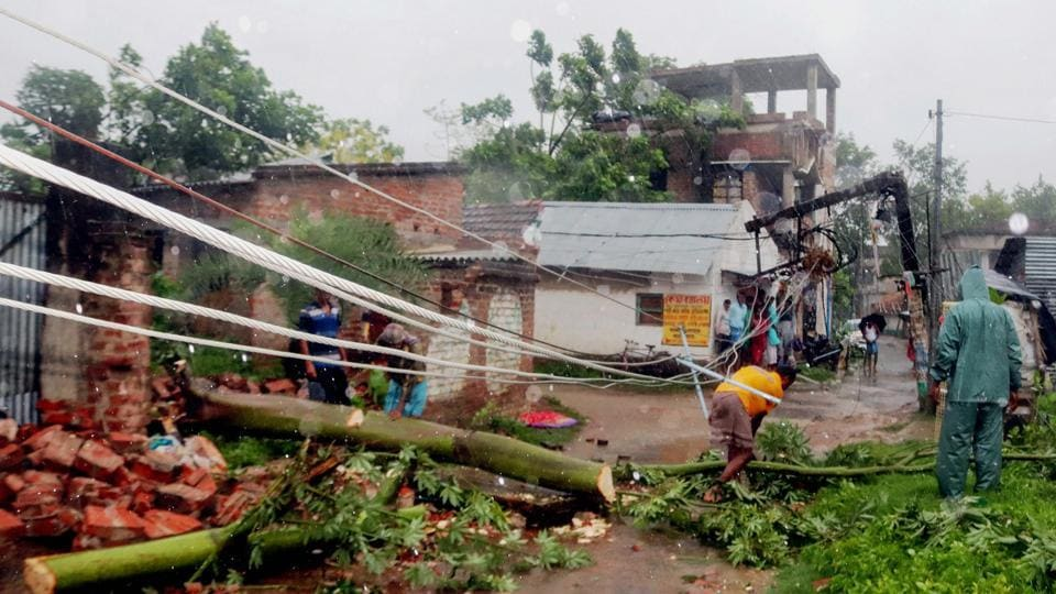 Workers try to restore a power line after a tree fell on it during a storm due to Cyclone Amphan, in Burdwan district of West Bengal.