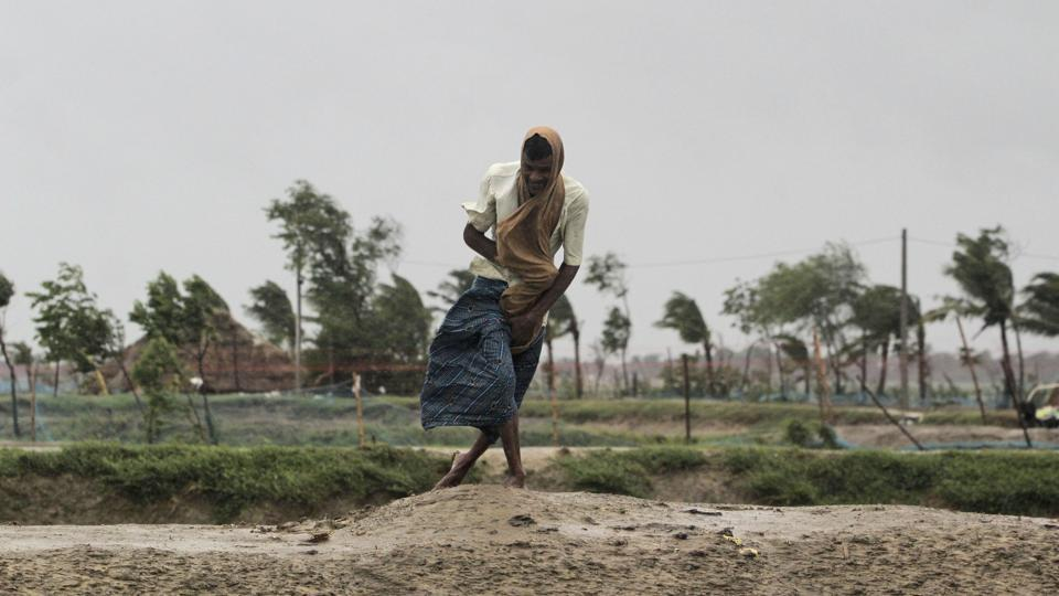 A man walks against the force of the wind in Bhadrak district, Odisha on May 20. The landfall process has triggered intense rain and gusty winds and will continue for about four hours, according to the India Meteorological Department (IMD). (AP)
