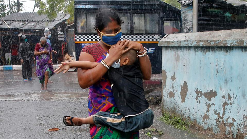A woman in Kolkata carries her son as she tries to protect him from heavy rain while they rush to a safer place, following their evacuation from a slum area just before Cyclone Amphan made its landfall in West Bengal this afternoon. At 3:05 pm, the wind speed at Kolkata airport was recorded at 76 km per hour, the meteorological office told HT. (Rupak De Chowdhuri / REUTERS)