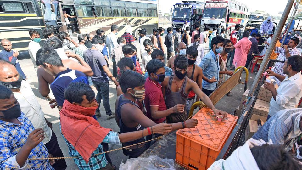 Migrants collect food from a stall at Indore bypass as they travel from Maharashtra and Gujarat to reach their native places in Uttar Pradesh, during the ongoing Covid-19 lockdown, in Indore on Tuesday.