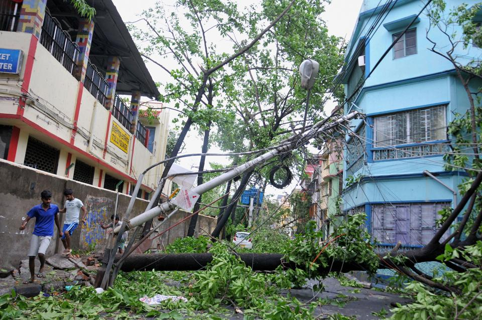 People walk past a damaged electrical pole on a road, in the aftermath of super cyclone 'Amphan', in Kolkata.