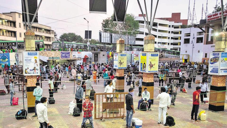 Stranded migrants maintain social distancing at Pune railway station in Pune, on Tuesday.