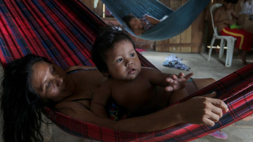 Priscila Tavares Batista, 36 lies in a hammock with her son Jone Tavares, 2, after being treated with medicinal herbs for symptoms of COVID-19, in the Wakiru community. The virus has infected 40 indigenous groups with 537 positive cases and 102 deaths according to the Brazilian Indigenous Peoples' Association, AFP reported on May 19. (Ricardo Oliveira / AFP)