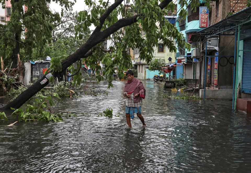 A man crosses a flooded street after Cyclone Amphan, Kolkata, May 21, 2020