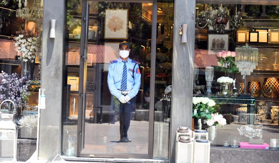 A security guard wears a face masks as he is seen outside a shop at Khan Market, after government eased lockdown restriction, in New Delhi, India, on Wednesday, May 20, 2020.