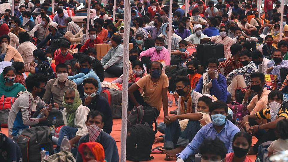 Stranded Bihar-bound migrant workers wait to be screened for body temperature inside a Delhi government school in Vinod Nagar, before being taken to board Shramik Special trains to their homes.   (Raj K Raj / HT Photo)