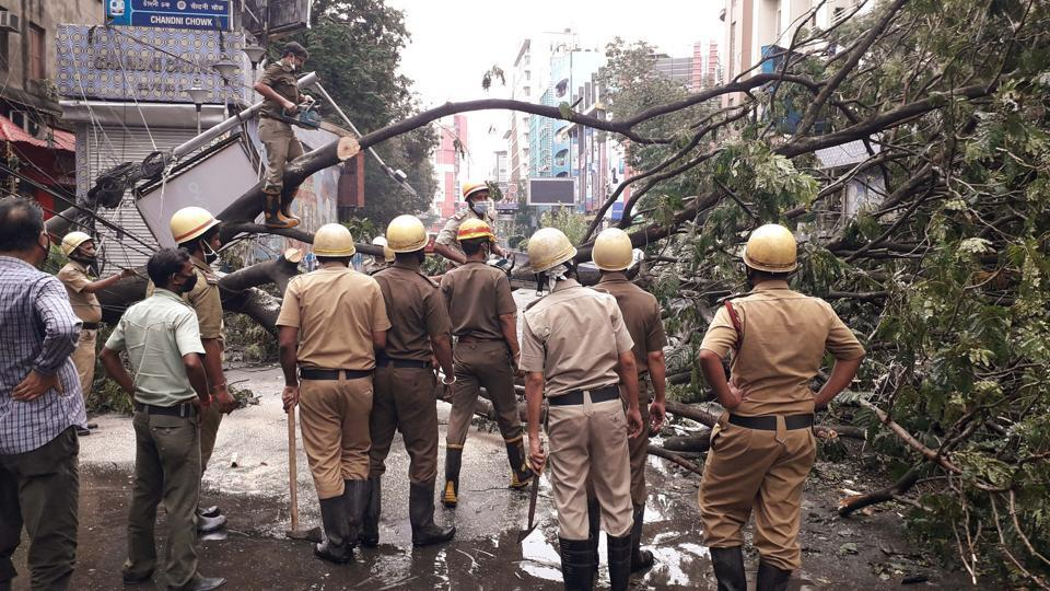 Fire brigade personnel removing the tree which got uprooted during the landfall of cyclone Amphan, in Kolkata on May 21, 2020.