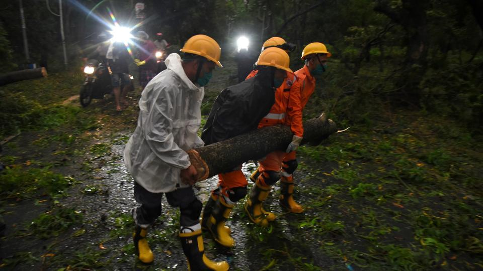 Members of National Disaster Rescue Force (NDRF) remove a branch of an uprooted tree after Cyclone Amphan made its landfall, in Digha, near the border between the eastern states of West Bengal and Odisha, India, May 20, 2020.