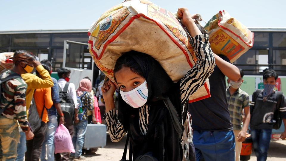 A girl carrying her belongings walks with her family members to get token to board a train to their home state of eastern Bihar, during an extended lockdown to slow the spreading of the coronavirus disease (Covid-19), in Ahmedabad, India, May 20, 2020.