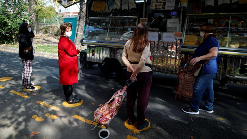 People queue following social distance rules as a preventive measure against the spread of the coronavirus disease (COVID-19) at a street market, in Buenos Aires, Argentina May 20, 2020.