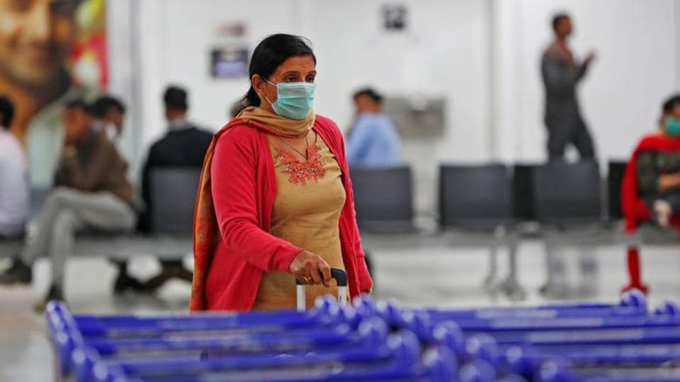 A passenger wearing a protective mask inside an airport terminal.