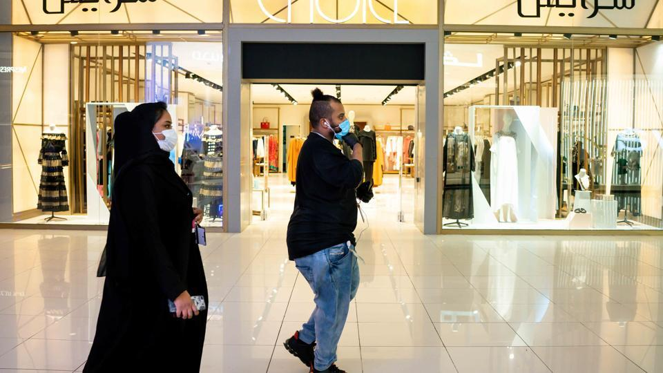 Pedestrians wear protective face masks while visiting a shopping mall and open retail stores in Riyadh, Saudi Arabia, on Tuesday, May 19. 2020. Before the pandemic, most shops, pharmacies and gas stations in the kingdom halted for at least 30 minutes for each prayer session, the only country that enforced such closures.