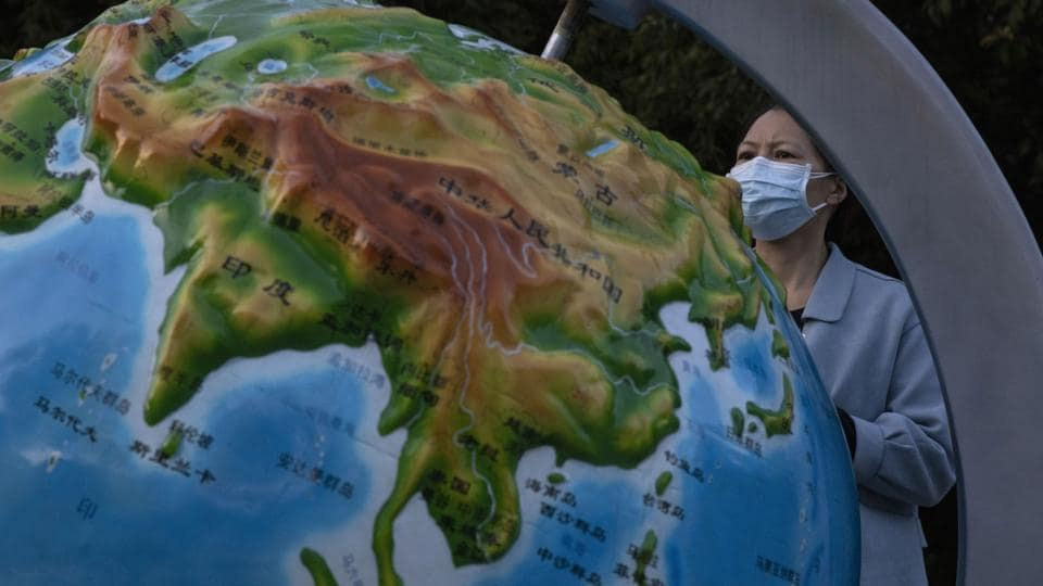 A  woman wearing a mask against the coronavirus looks at a globe showing China, in Wuhan in central China's Hubei province.