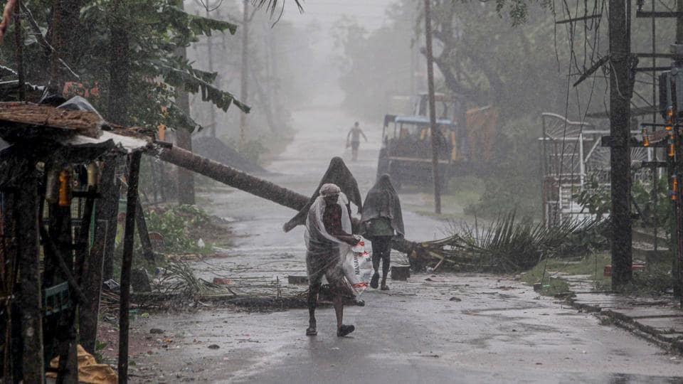 People make way through gusty winds as super cyclone Amphan makes landfall, near Dhamara Port in Bhadrak district, Wednesday, May 20, 2020.