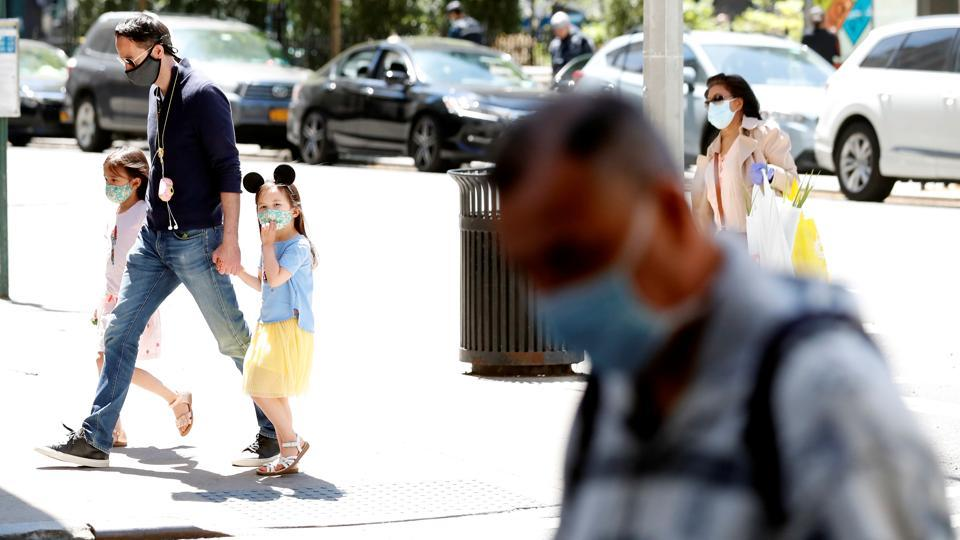 A man holds the hands of two young girls wearing masks as they cross the street as residents of New York City adjust to living with the ongoing outbreak of the coronavirus disease in the Manhattan borough of New York on Wednesday.