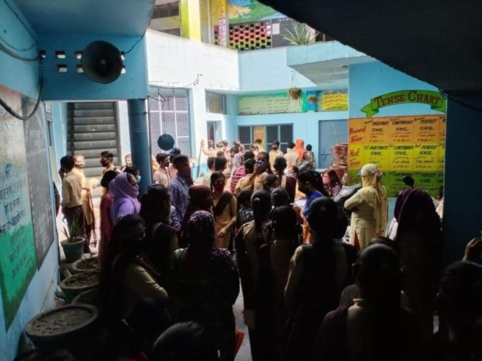 Parents and students gather at Government High School, Kailash Nagar, to collect textbooks on Friday.