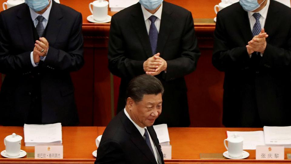 Chinese President Xi Jinping walks past officials wearing face masks following the coronavirus disease (Covid-19) outbreak as he arrives for the opening session of the National People's Congress (NPC) at the Great Hall of the People in Beijing.