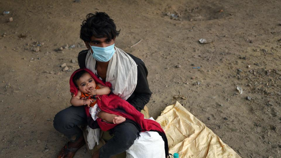 A migrant worker with his four month old daughter at Ghazipur border, in New Delhi.