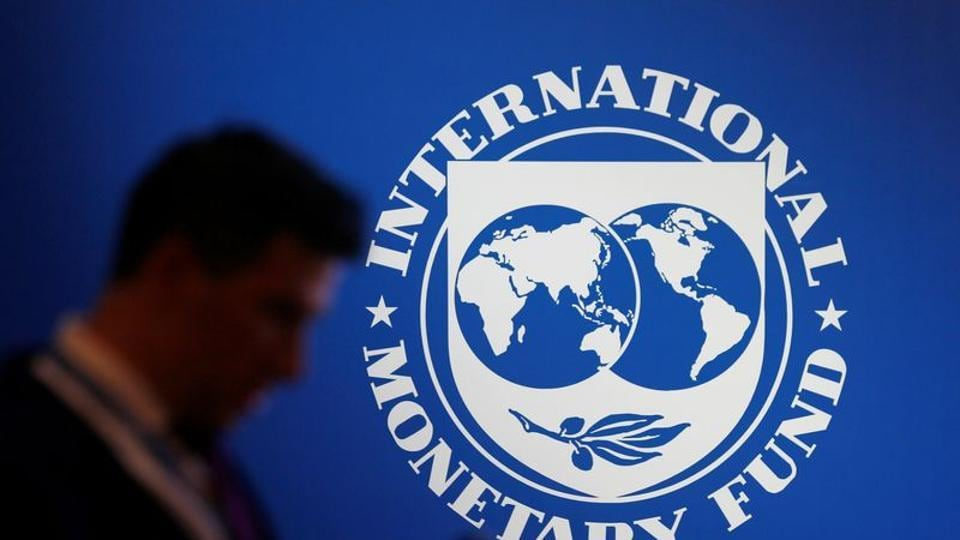 A participant stands near a logo of IMF at the International Monetary Fund - World Bank Annual Meeting 2018 in Nusa Dua, Bali, Indonesia.