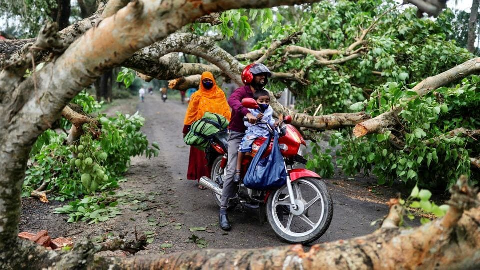 A man with a child ride on motorbike in the street blocked by trees that were uprooted by the cyclone Amphan, in Satkhira, Bangladesh May 21, 2020.