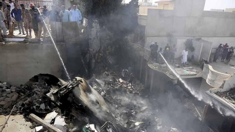 Fire brigade staff try to put out fire caused by plane crash in Karachi, Pakistan on Friday.