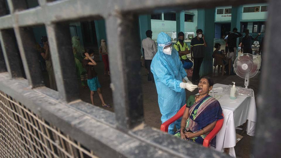A healthcare worker collects oral swab sample of a woman for Covid-19 test, at Sane Guruji Smarak, during lockdown, Sinhagad road, in Pune, India, on Thursday, May 21, 2020.