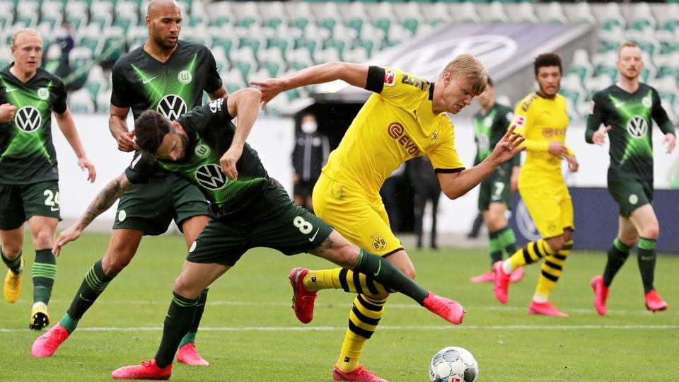 Borussia Dortmund's Erling Haaland in action with VfL Wolfsburg's Renato Steffen.