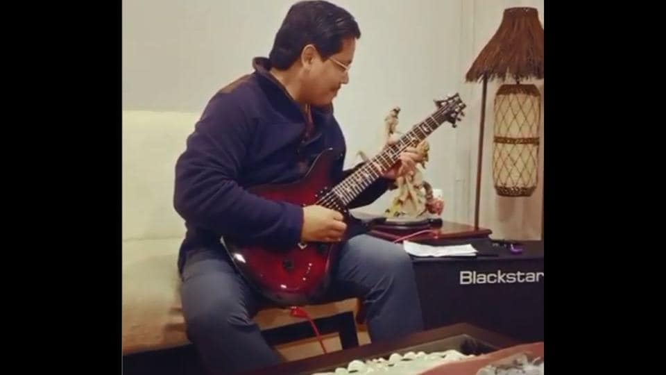 The image shows Meghalaya CM Conrad Sangma playing his guitar.