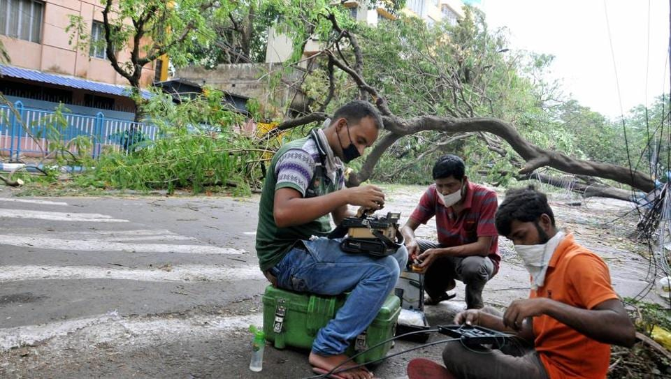 Cable TV engineers work to restore the services that were destroyed due to Super Cyclone Amphan, in Kolkata, Friday, May 22, 2020.