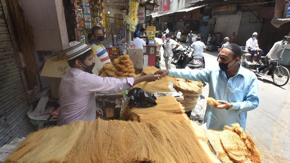 People seen at shops open for business ahead of Eid ul-Fitr festival at Jama Masjid in New Delhi.