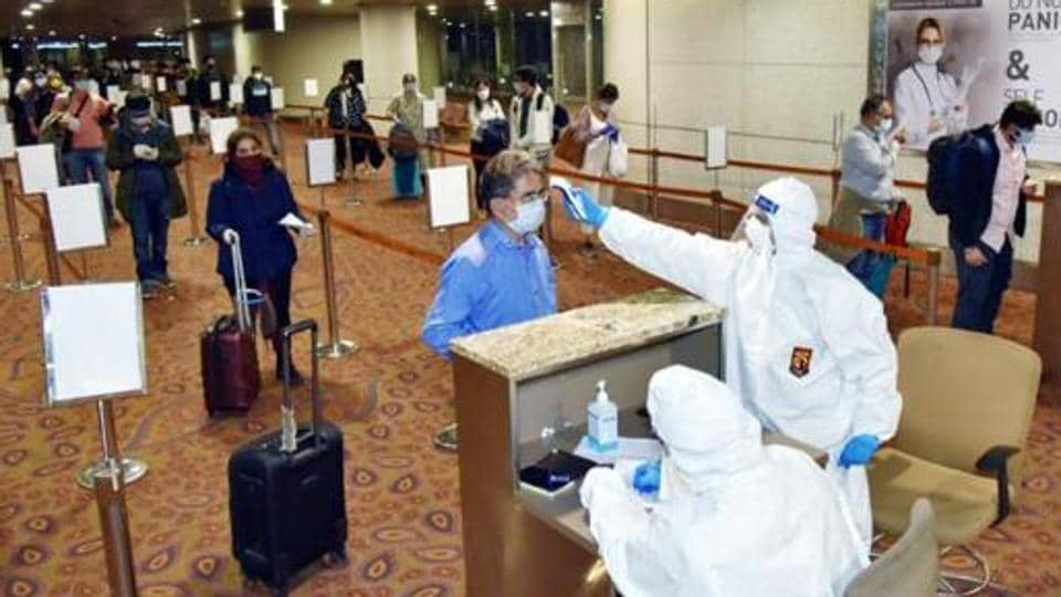 Doctors conduct the thermal screening of the Indian nationals from London after they arrive via special flight under Vande Bharat Mission in Mumbai.