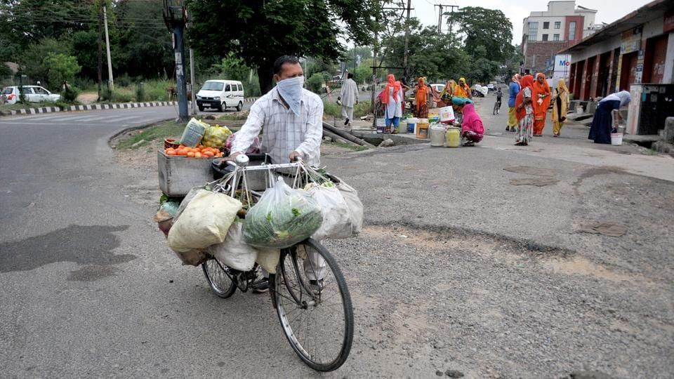 A vegetable vendor pushes his cycle past migrant women filling containers with water a roadside tap during lockdown in Jammu, Jammu and Kashmir on Friday.